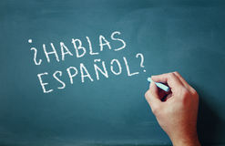 The question do you speak espanol written on chalkboard and male hand Royalty Free Stock Photo