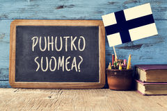Question do you speak Finnish? written in Finnish. A chalkboard with the question puhutko suomea, do you speak Finnish? written in Finnish, a pot with pencils Royalty Free Stock Photo