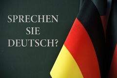 Question do you speak german, in german. Some flags of germany and the question sprechen sie deutsch?, do you speak german? written in german, against a dark Stock Photos