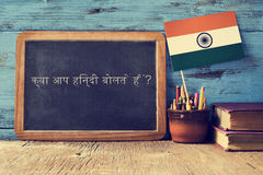 Question do you speak hindi? written in hindi. A chalkboard with the question do you speak hindi? written in hindi, a pot with pencils, some books and the flag Stock Photo