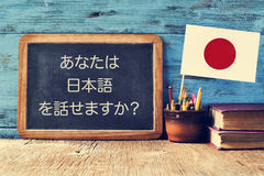 Question do you speak Japanese? written in Japanese. A chalkboard with the question do you speak Japanese? written in Japanese, a pot with pencils, some books Royalty Free Stock Images