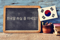 Question do you speak Korean? written in Korean. A chalkboard with the question do you speak Korean? written in Korean, a pot with pencils, some books and the Royalty Free Stock Images