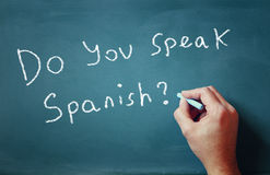 The question do you speak spanish written on chalkboard and male hand Royalty Free Stock Photos