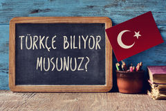 Question do you speak Turkish? written in Turkish. A chalkboard with the question turkce biliyor musunuz?, do you speak Turkish? written in Turkish, a pot with Stock Image
