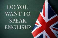 Question do you want to speak English?. A flag of the United Kingdom and the question do you want to speak English? against a dark green background Royalty Free Stock Images