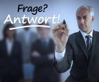 Question et réponse d'écriture d'homme d'affaires en allemand photographie stock