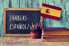 Question hablas espanol? do you speak Spanish?. A chalkboard with the question hablas espanol? do you speak Spanish? written in Spanish, a pot with pencils and Stock Photo