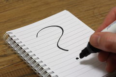 Question mark being written on paper. A question mark is written on paper with a black marker, indicating uncertainty Stock Photography