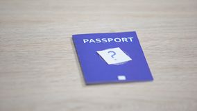 Question mark on blue international passport table, travel document, citizenship. Stock footage stock video footage