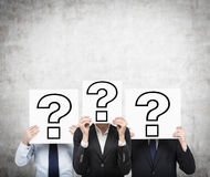 Question mark. Businesspeople holding poster with drawing question mark Royalty Free Stock Images