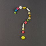 Question mark created from colored pills. Medical concept Stock Photos