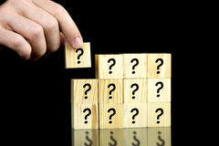 Question mark cubes. Male hand placing last piece of a cube with question mark Stock Photography