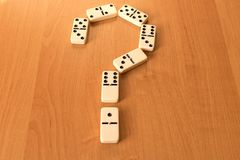 Question mark of dominoes knuckles on wooden background.  Royalty Free Stock Photo