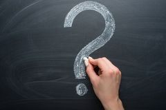 Question mark, drawn chalk on a blackboard with a girl& x27;s hand.  royalty free stock images