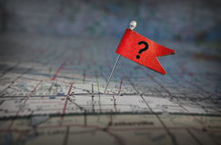 Question mark flag on a map. Pin with red question mark flag stuck in a map Royalty Free Stock Image