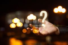 Question mark in hand . Question mark in hand on the background of night city. The concept answers to the questions Royalty Free Stock Photography