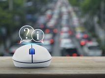 Customer support concept. Question mark and information chat icon with wireless computer mouse on wooden table over blur of rush hour with cars and road Royalty Free Stock Photography