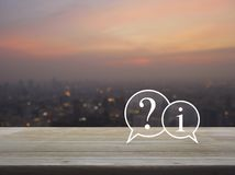 Customer support concept. Question mark and information chat icon on wooden table over blur of cityscape on warm light sundown, Customer support concept royalty free stock photography