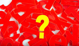 Question mark letter closeup. Find Question mark in yellow letters on a background of red letter in a jumble or word search puzzle Stock Image
