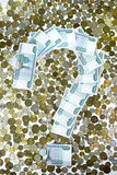The question mark is lined with notes on the background of the coins Stock Image