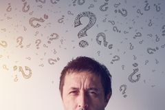 Question mark, looking for answers. Perplexed man with scribbled interrogation point symboles around his head stock images