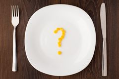 Question mark made of corn seeds on plate Stock Photos
