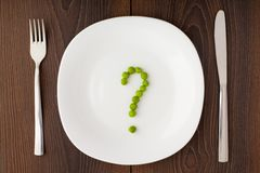 Question mark made of peas on plate Stock Photo