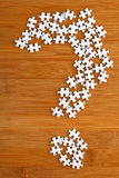 Question mark made by puzzle on wood background. Question mark made by puzzle on the wood background Stock Photo