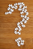 Question mark made by puzzle on wood background. Question mark made by puzzle Royalty Free Stock Photo