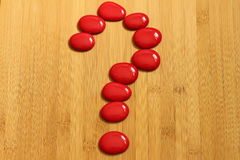A question mark made with red pebbles in Zen lifestyle on a brown bamboo floor. Question mark made with red pebbles in Zen lifestyle on a brown bamboo floor royalty free stock image