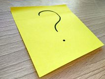 Question mark message on yellow sticky note on wooden background. Question mark message on yellow sticky note on wooden table background royalty free stock photo