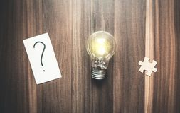 Question mark in paper with puzzle and light bulb on a wood back. Ground Stock Photography