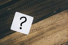 Question mark. On white note on a wooden background. mystery,what,when,why,who and when stock photos