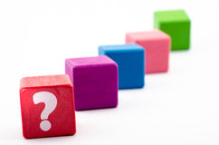 Question mark on red brick. Five colored bricks in a diagonal row with a prominent red one inscribed with a question mark, white background Royalty Free Stock Photos