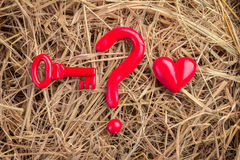 Question mark with red key and heart object on hay texture Royalty Free Stock Photos