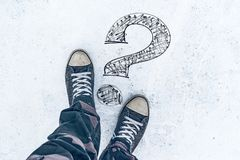Question mark on the road and sneakers. Wondering and asking questions royalty free stock images