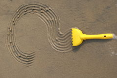 Question mark on sand. The question mark on sand is written by a toy rake Royalty Free Stock Image