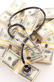 Question Mark Shaped Stethoscope Laying on Money. Question Mark Shaped Stethoscope Laying on Stacks of Hundred Dollar Bills with Narrow Depth of Field Royalty Free Stock Image