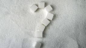 Question mark spelled out in sugar cubes forming on pile of sugar