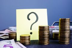 Question mark and stacks of coins. Business uncertainty. royalty free stock photography