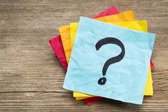 Question mark on sticky note. Question mark on a sticky note against grained wood royalty free stock photo