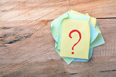 Question mark sticky note. On wood stock image