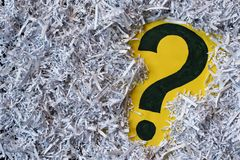 Question mark symbol in a shredded paper. Concept of confidential office paperwork, faq and questions stock photo