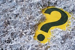 Question mark symbol in a shredded paper. Concept of confidential office paperwork, faq and questions stock images