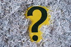 Question mark symbol in a shredded paper. Concept of confidential office paperwork, faq and questions stock photography
