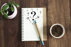 Question mark symbols in notebook. Laying on office desk. flat lay view royalty free stock image