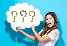 Question Mark text with young woman holding a speech bubble Royalty Free Stock Image