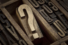 Question mark in vintage letterpress type. Question mark - vintage wooden letterpress type block in old typesetter drawer among other letters, sepia toned black royalty free stock images