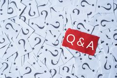 Question mark on white paper and Q&A on red paper. Questions and answer concept stock image