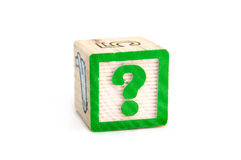 Question mark on wooden block. Closeup of green question mark on wooden toy block, isolated on white background Stock Images